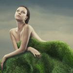 Une femme nue derrière une butte d'herbe