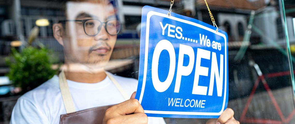 Un jeune homme portant des lunettes et un tablier ouvre sa boutique