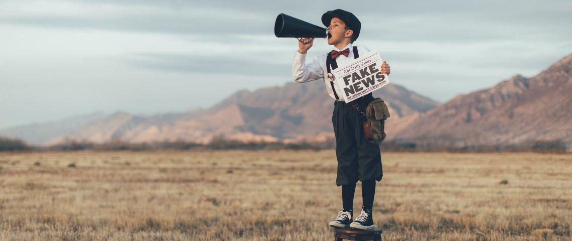 Un enfant avec un mégaphone et un journal où il est écrit Fake News