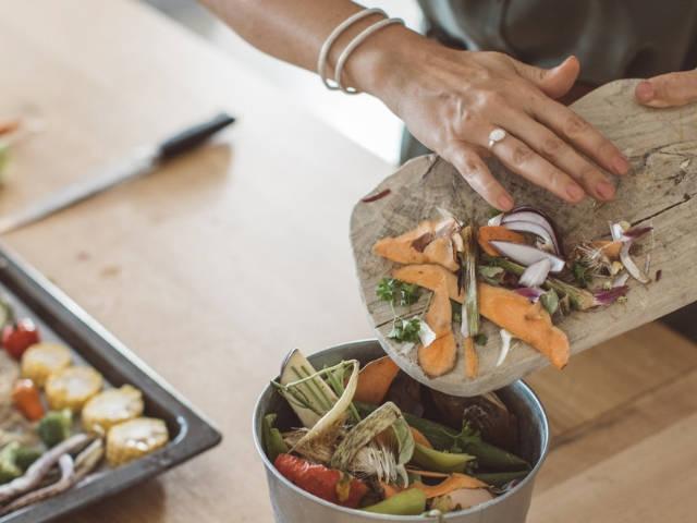 Une femme en train de jeter des épluchures de légumes