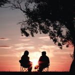 deux jeunes qui parlent assis face au coucher du soleil