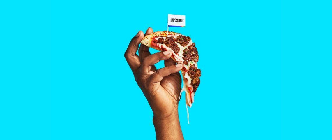 Une main qui tient une pizza avec de la viande végétale sur un fond bleu