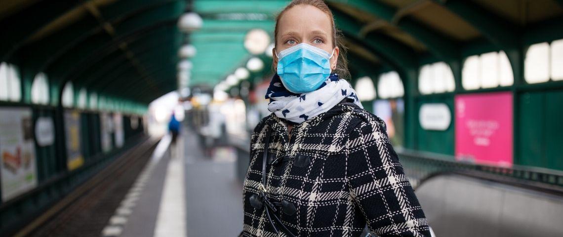 Une masque avec un masque qui attend le métro