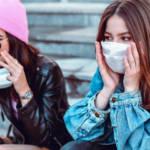 Deux jeunes filles portant un masque sur des escaliers