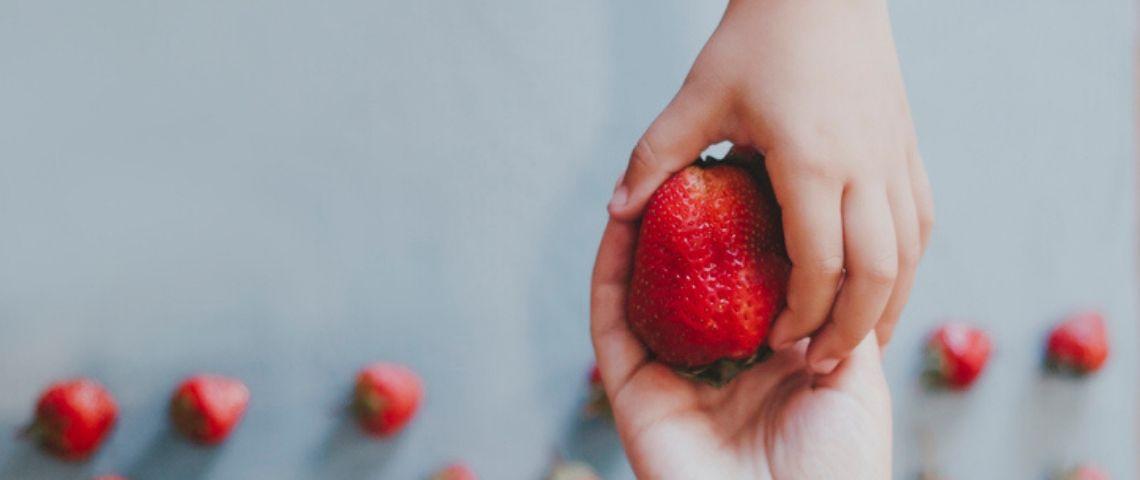 Un enfant donne une fraise