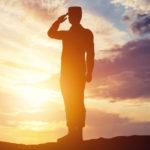 Un officier faisant un salut sur un fond de soleil couchant