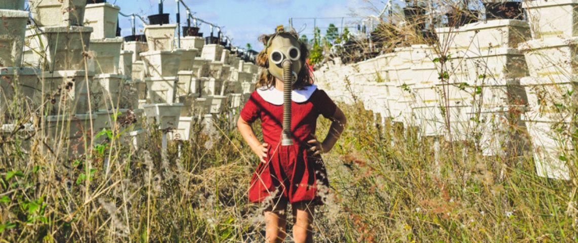 Une petite fille dans un champ avec un masque futuriste