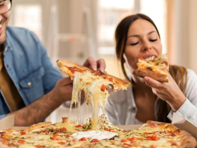 Un homme et une femme en train de manger une pizza