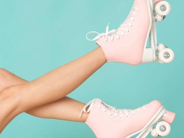Des jambes avec des patins à roulettes roses