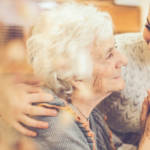 Une vieille femme avec une plus jeune femme en train de se tenir la main