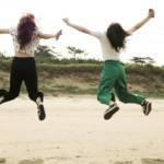 Deux femmes qui sautent en l'air sur une plage