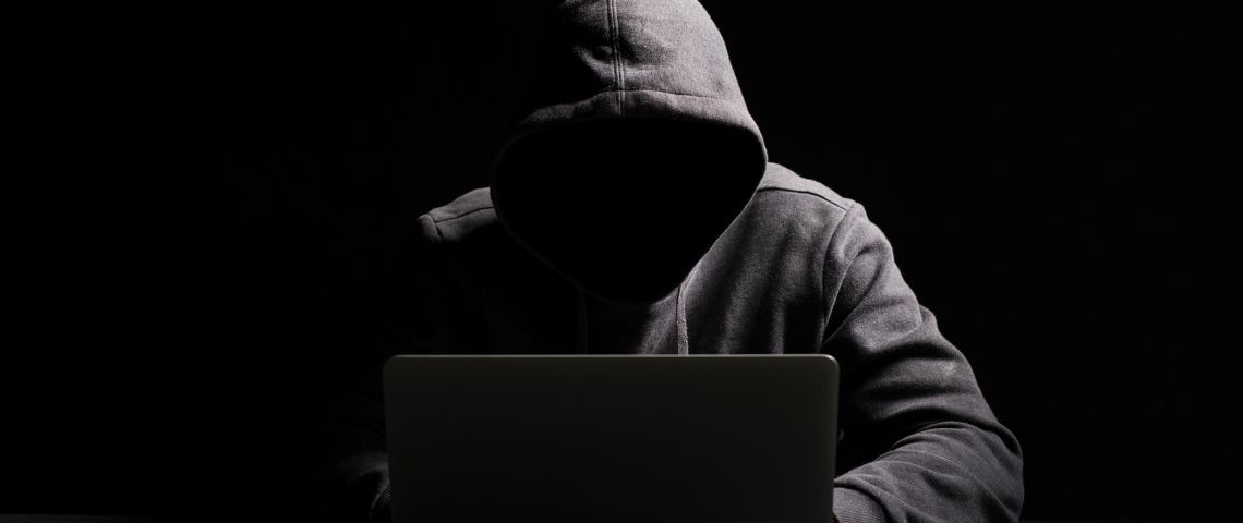 Un homme avec une capuche dans le noir devant son ordinateur