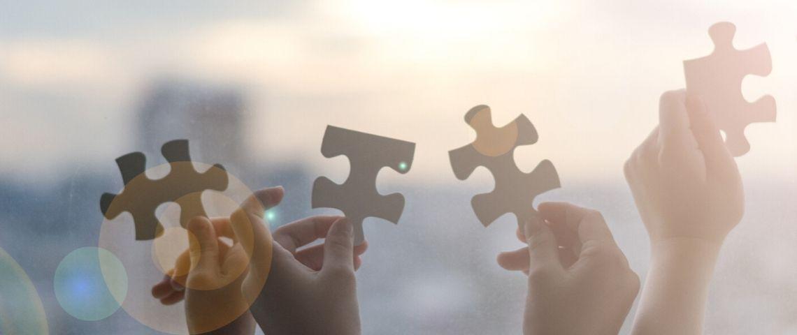 des mains qui tiennent des pièces de puzzle