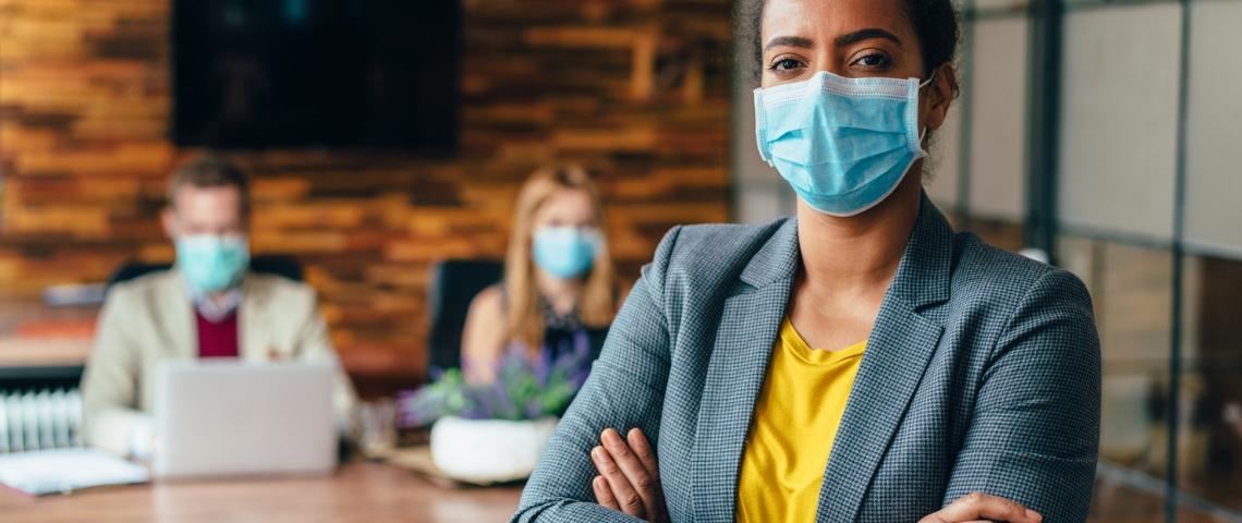 Une femme noire portant un masque chirurgical au bureau