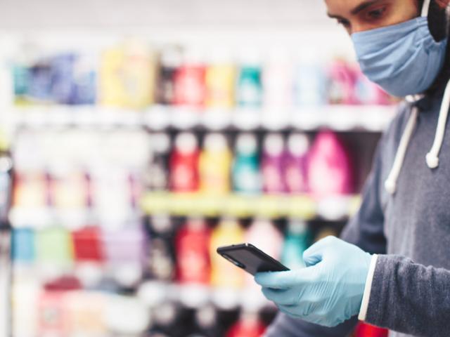Homme portant un masque dans un supermarché en regardant son smartphone