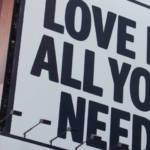 """Un panneau publicitaire avec écrit """"Love is all you need"""""""