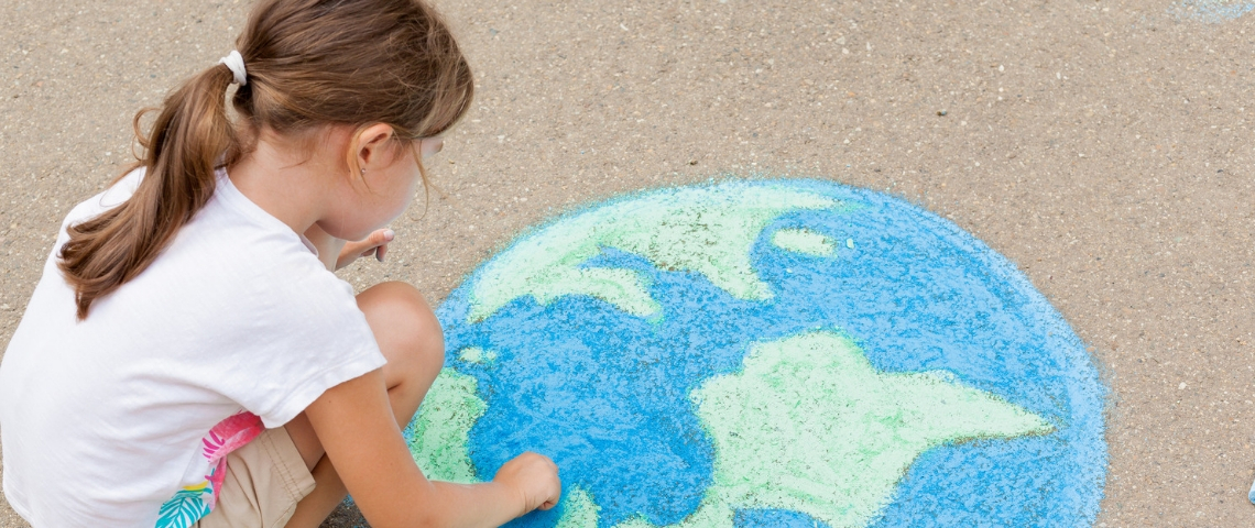Une petite fille en train de dessiner une terre à la craie au sol