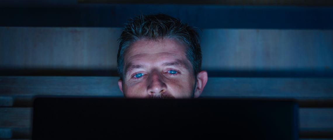 Homme devant un ordinateur de nuit