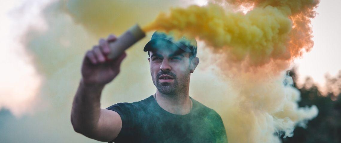 un homme blanc manifestant avec un fumigène