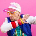 Une grand-mère qui danse sur un fond rose