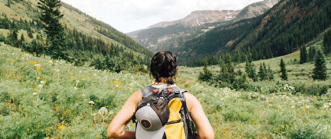 Une femme de dos avec un sac de randonnée