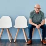 Un homme d'âge mur sur une chaise seul fond bleu