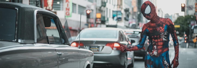 Un homme déguisé en Spider Man en train de faire du stop