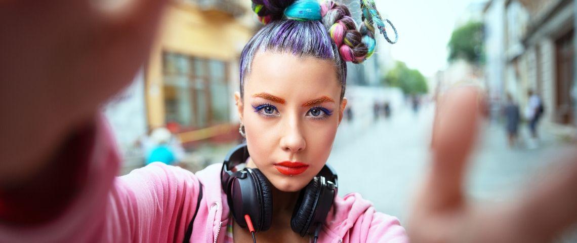 Une femme avec les cheveux colorés qui regarde la caméra