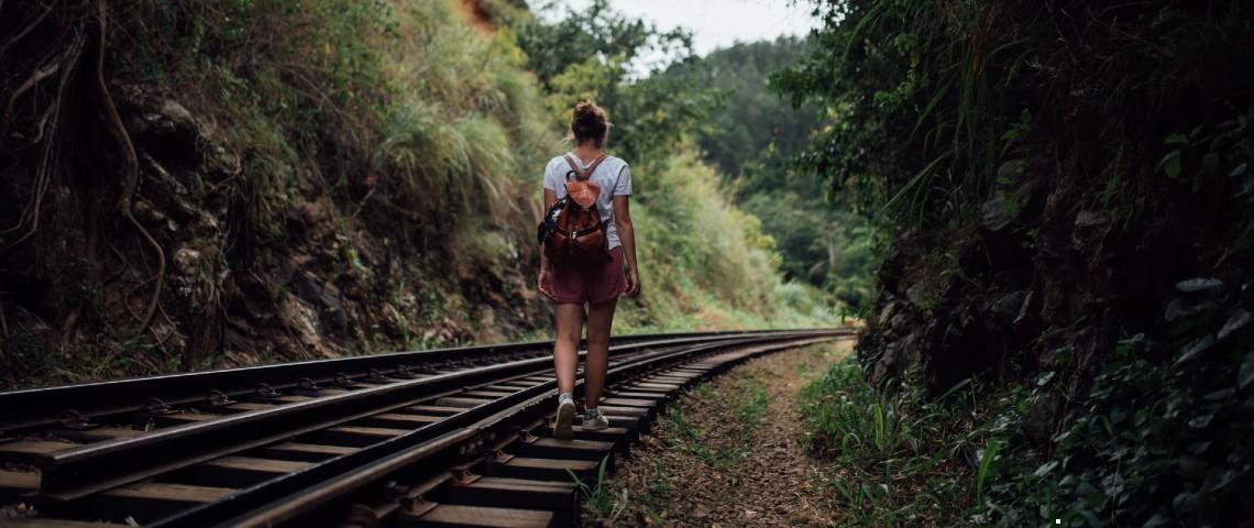 Une jeune femme marche sur des rails de trains entourés de verdure
