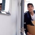 Un jeune homme avec un carton de déménagement qui rentre dans une maison