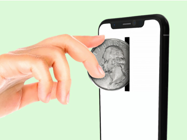 une main insérant une pièce de monnaie dans un smartphone