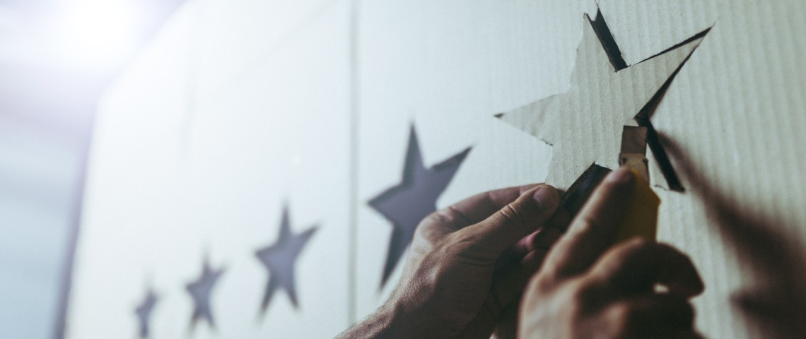 Homme en train de fixer une étoile en carton
