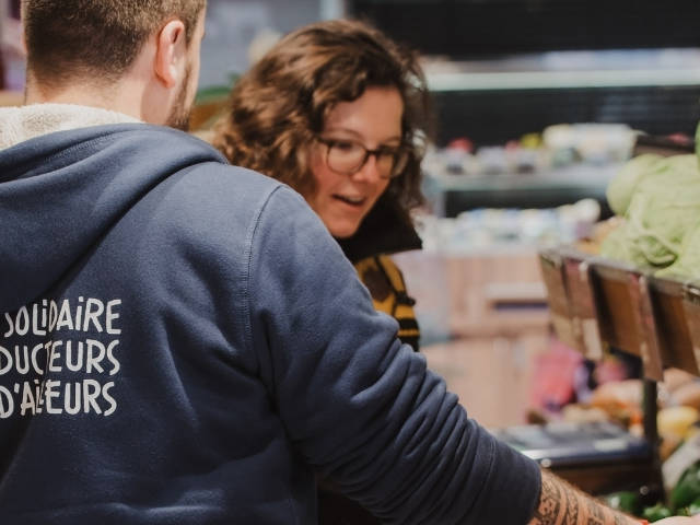 Une femme en train d'acheter des fruits et légumes chez Biocoop se faisant aider par un vendeur