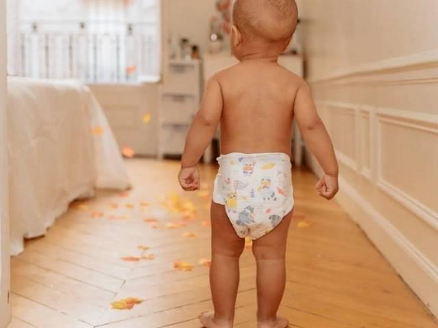Bébé marchand de dos avec une couche