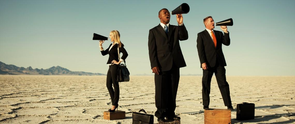 Trois personnes en costume avec mallettes parlent dans des haut parleurs
