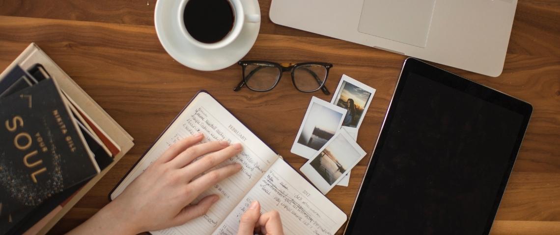 Une femme écrivant dans un carnet avec une tasse de café