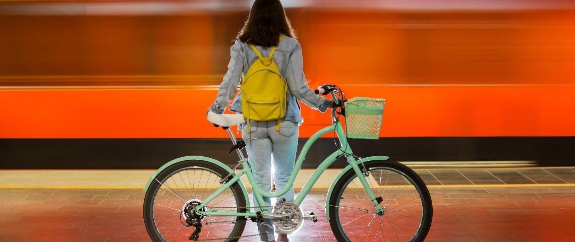 Une femme de dos avec un vélo devant un fond rouge