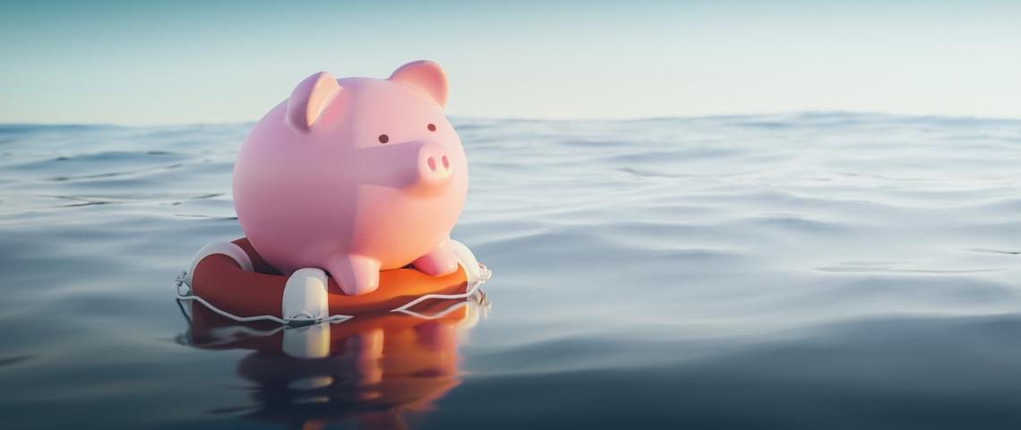 Une tirelire cochon sur une bouée, à la mer