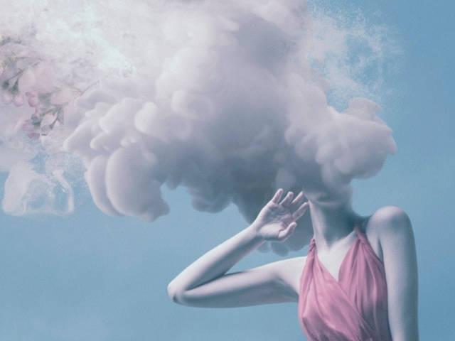 Une femme avec la tête dans de la fumée rose