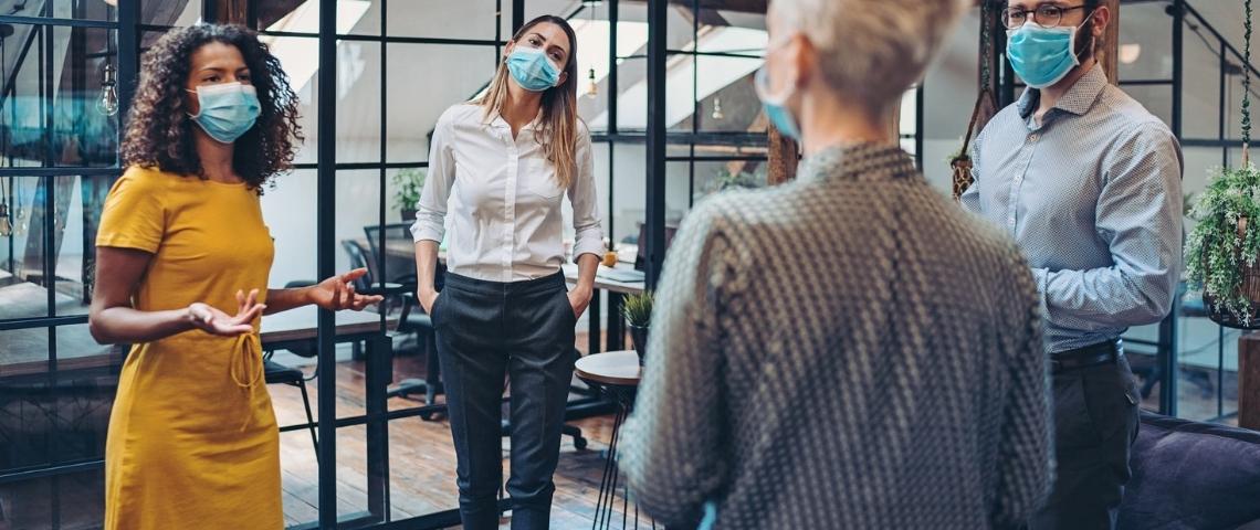 Une femme en réunion avec ses employés, portant un masque, en entreprise
