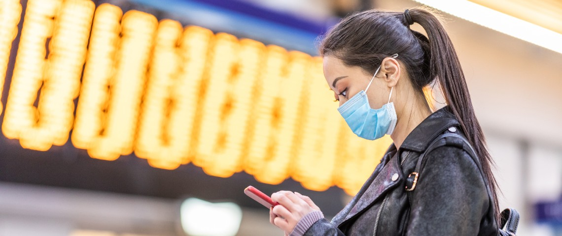 femme chinoise porte un masque et regarde son smartphone