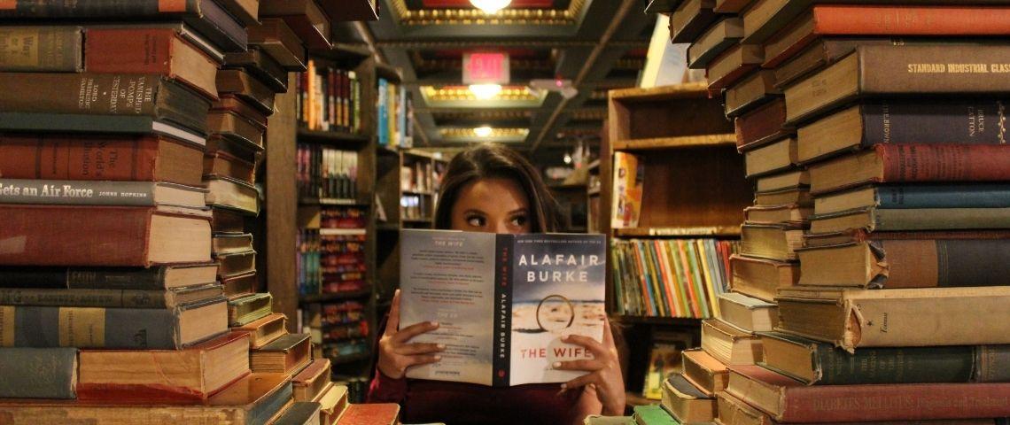 une femme lit dans une bibliothèque