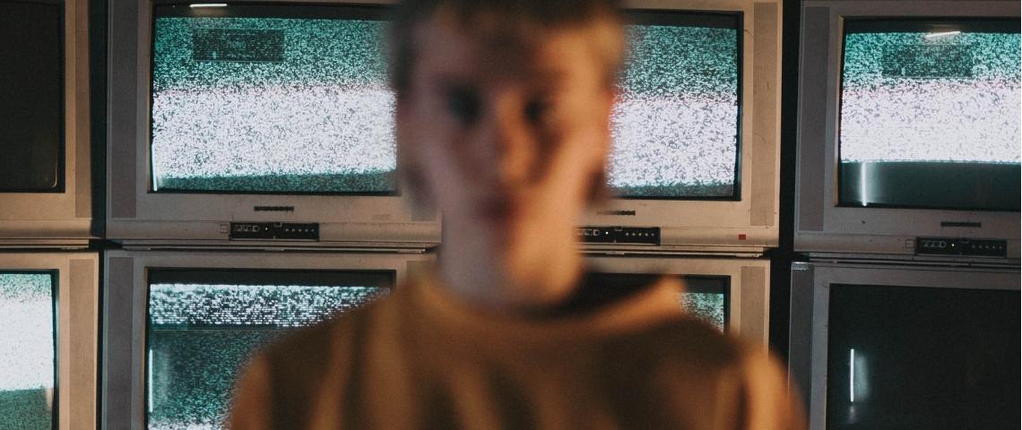 une femme floutée devant des écrans de télévision