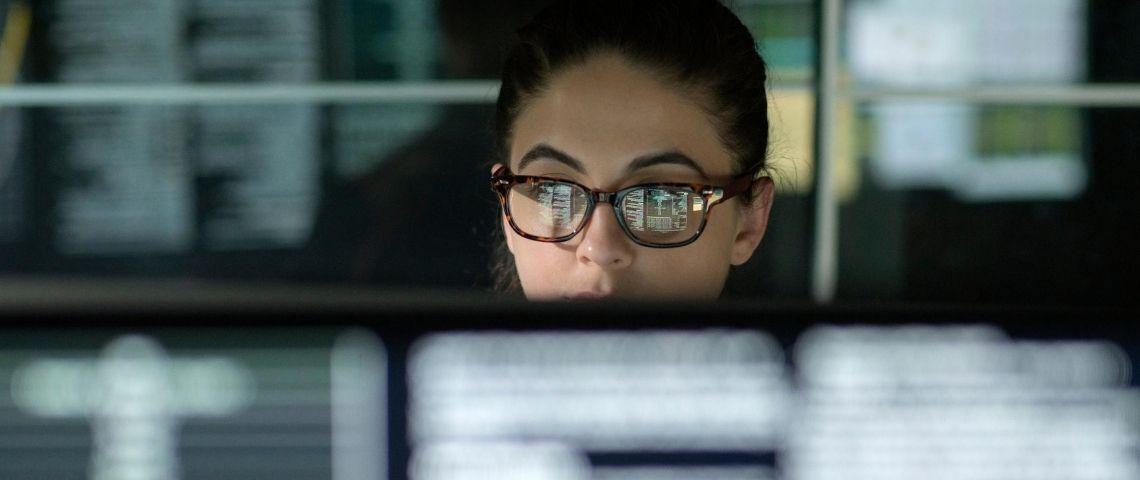 Une femme derrière un ordinateur avec plein de data