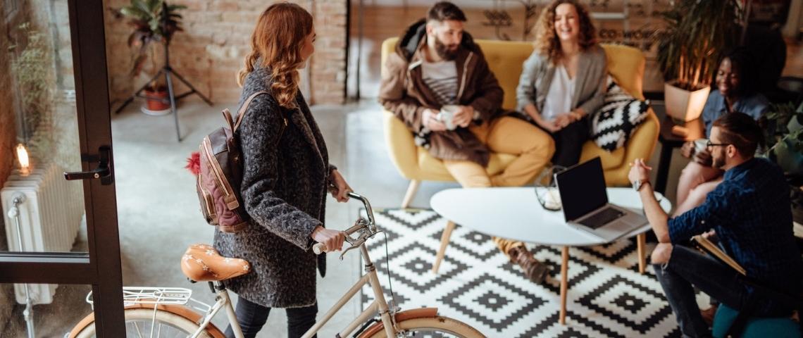 Une femme entrant dans son bureau avec son vélo