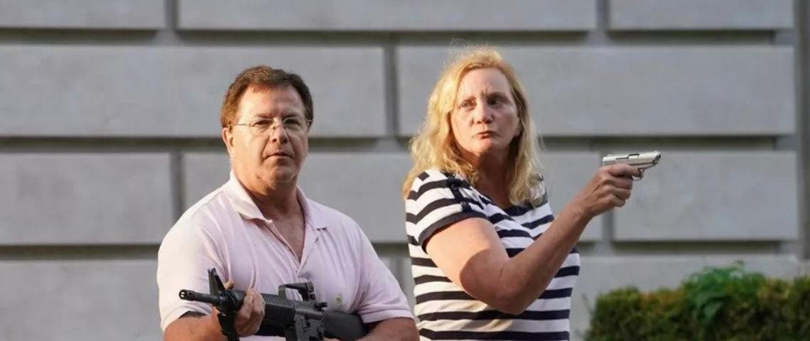 un homme et une femme menace de leur arme une foule de manifestants