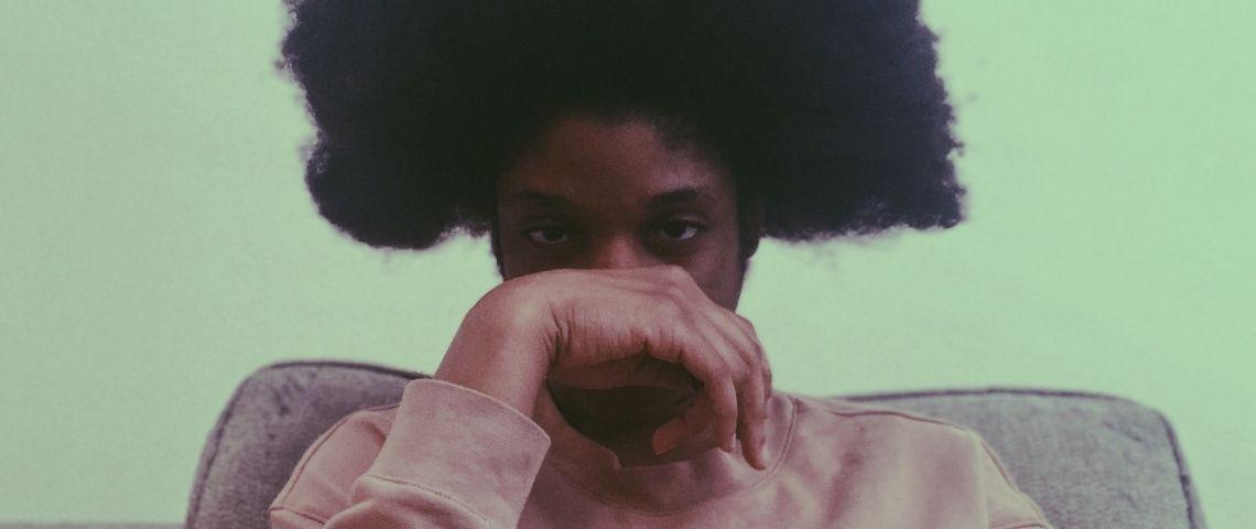 Un jeune homme noir avec une coupe afro et sa main devant le visage