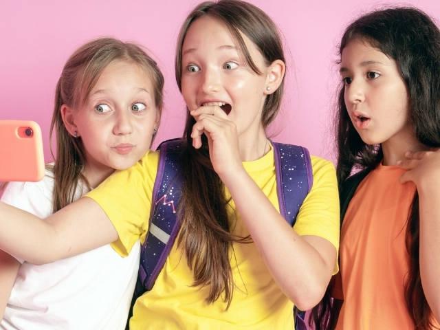 trois adolescentes qui regardent leur portable