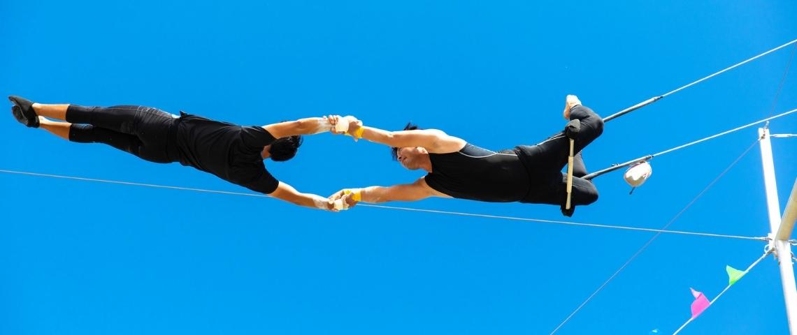 Deux trapézistes en train de faire des acrobaties