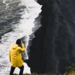 uUn homme en ciré jaune regarde une vague